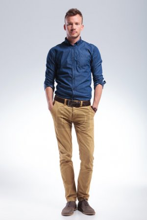 Photo for Full length picture of a casual young man standing with his hands in his pockets while looking into the camera with a serious expression. on gray background - Royalty Free Image