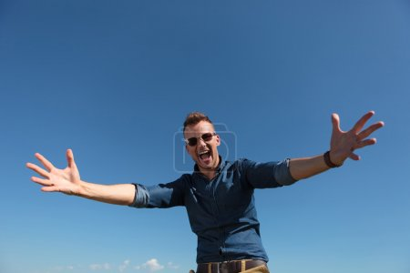 Casual young man outdoor wanting to hug the camera...