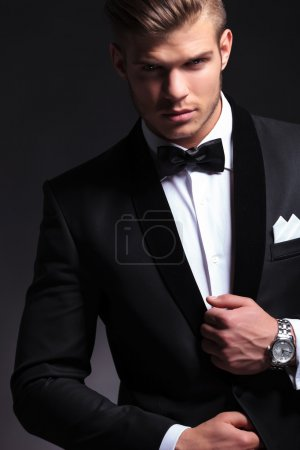 Photo for Cutout picture of an elegant young fashion man fixing his tuxedo while looking at the camera.on black background - Royalty Free Image