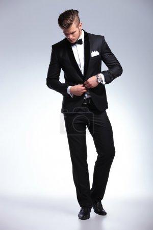 Photo pour Photo pleine longueur d'un élégant jeune homme de mode en smoking boutonnant sa veste tout en regardant vers le bas, loin de l'appareil photo. sur fond gris - image libre de droit