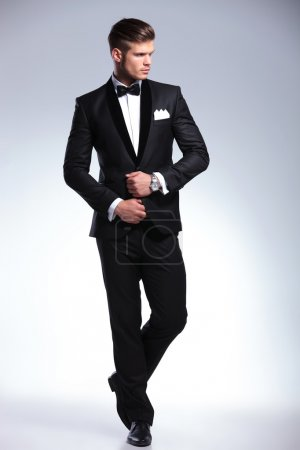 Photo for Full length picture of an elegant young fashion man adjusting his tuxedo while looking to his side, away from the camera. on gray background - Royalty Free Image