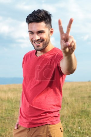 Casual man shows victory sign