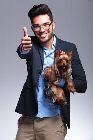 casual young man holds puppy and shows thumb up