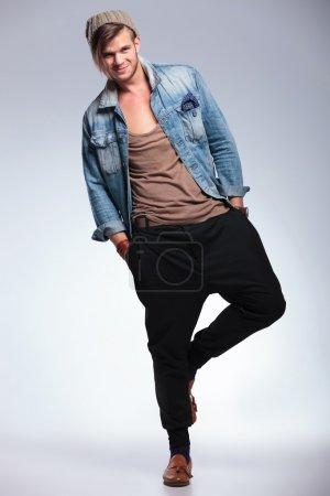 full length of casual man smiling on one leg