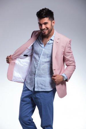 casual man takes off jacket and smiles