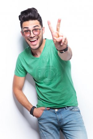 Photo for Young casual man showing the victory gesture while smiling for the camera with a hand in his pocket. on white background - Royalty Free Image