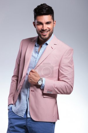 casual man smiles with hand on jacket