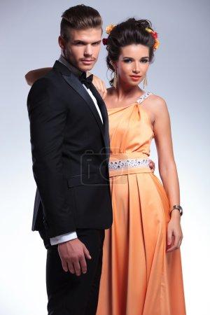 Photo pour Jeune couple de mode embrassant et regardant la caméra alors qu'elle tient sa main sur son épaule. sur fond gris - image libre de droit