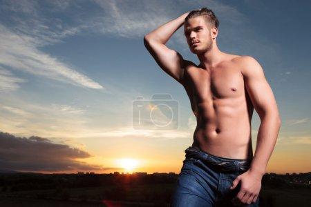 Topless man passes hand through hair at sunset