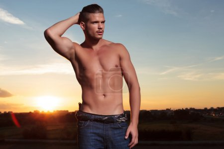 Topless man holds back his hair at sunset