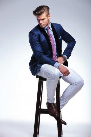 Photo pour Image pleine longueur d'un jeune homme d'affaires assis sur une chaise et regardant vers le bas tout en tenant une main sur sa hanche. sur fond gris - image libre de droit