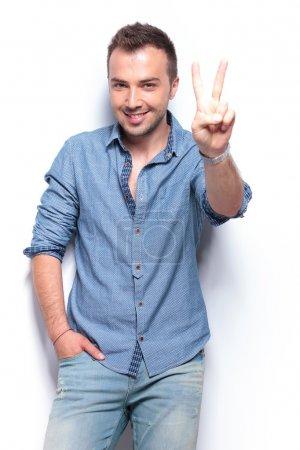 Photo pour Jeune homme décontracté montrant signe de victoire tout en tenant une main dans sa poche. sur fond blanc - image libre de droit