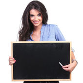 casual woman presents on blackboard with chalk