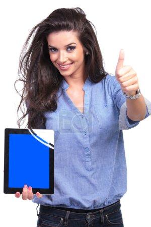 Photo pour Jeune femme casual présentant une tablette avec un écran bleu tout en montrant le pouce en haut signe avec un sourire pour la caméra. sur fond blanc - image libre de droit