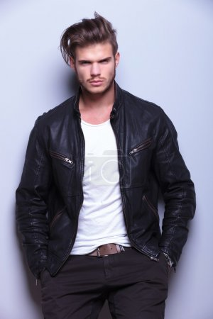serious man in leather jacket standing against gray wall