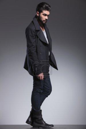 young bearded fashion man in a long coat looking away