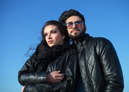 Pensive young couple standing against blue sky
