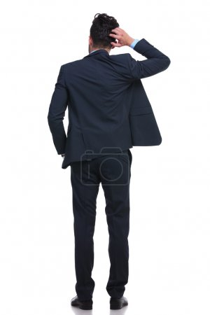 Photo pour Back of a young business man scratching his head trying to resolve a problem - image libre de droit