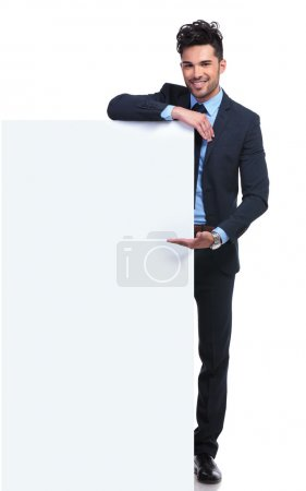 Photo for Smiling young man presenting a big blank billboard on white background - Royalty Free Image