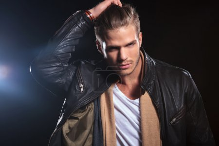 young fashion man passing his hand through his hair
