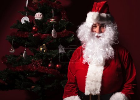 Photo for Santa claus is sitting near a christmas tree on red studio background - Royalty Free Image