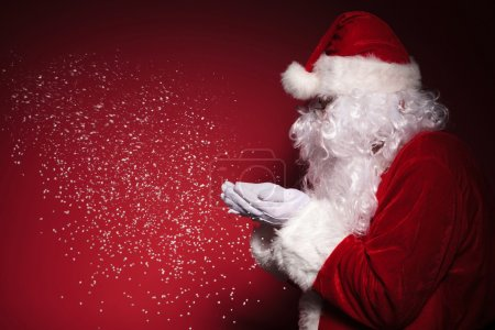 Photo for Side view of santa claus blowing snow on a red background - Royalty Free Image