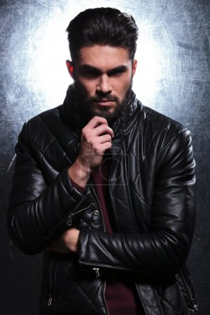Photo for Dramatic picture of a pensive fashion young man in leather jacket - Royalty Free Image