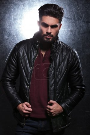 fashion man with long beard pulling on his leather jacket