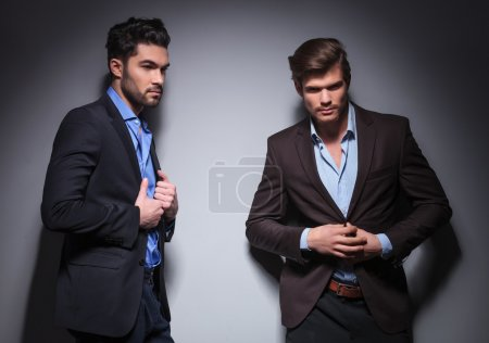 Photo for Two male fashion models posing in studio, one with shoulder against the wall looking away - Royalty Free Image