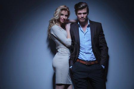 Photo pour Femme souriante debout contre son petit ami détendu avec les mains dans les poches - image libre de droit
