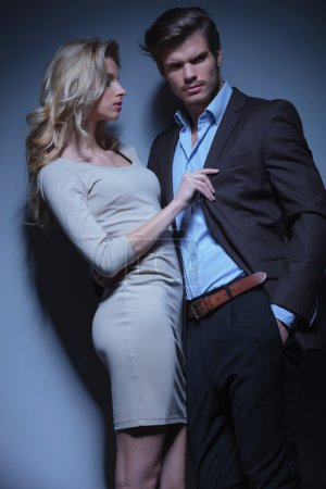 blonde woman pulling her man by his collar