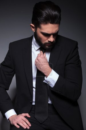 young fashion man looks down and fixes tie