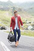 Mladý muž chodí s taškou na silnici