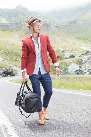 Photo pour Photo d'un jeune homme de mode marchant sur la route, dans les montagnes, avec un sac à la main tout en regardant loin de la caméra - image libre de droit