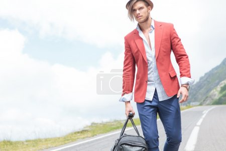young fashion man carries bag outdoor