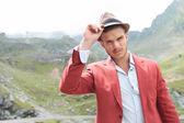 Venkovní módní muž drží ruku na klobouk