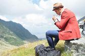 Mladý muž světla cigareta v horách