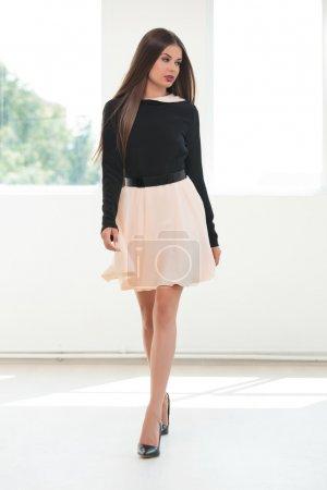 Photo pour Portrait complet d'une jeune femme de mode marchant vers la caméra dans un studio tout en regardant loin, de son côté - image libre de droit