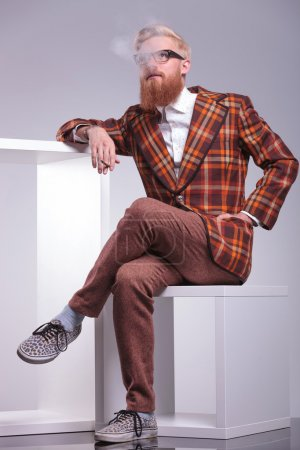 Side of a fashion man with beard blowing his smoke