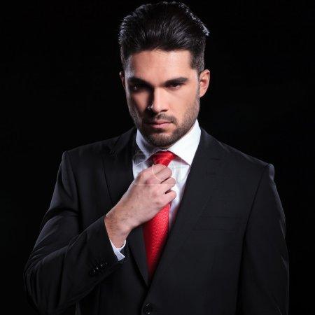 Photo pour Portrait d'un homme d'affaires jeune sérieux ajuster sa cravate tout en regardant la caméra. sur un fond noir - image libre de droit