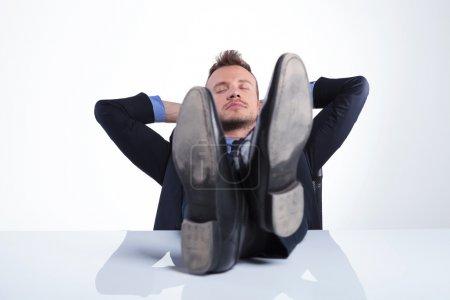 Photo pour Jeune homme d'affaires dormant les pieds sur le bureau et les mains derrière la tête. sur un fond studio gris clair - image libre de droit