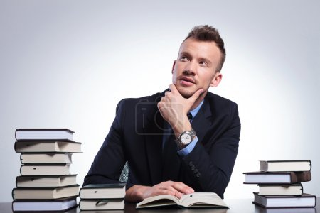 Business man thinks while reading