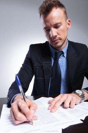 Photo pour Jeune homme d'affaires écrit quelque chose sur un formulaire. sur un fond studio gris clair - image libre de droit