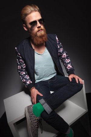 Young bearded hipster sitting with his feet crosse...