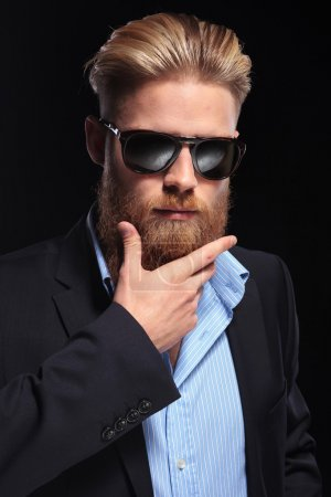 bearded business man with hand at chin