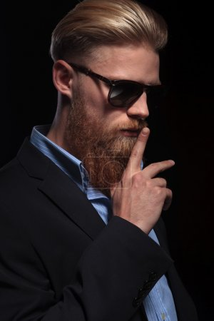 bearded business man with finger at mouth