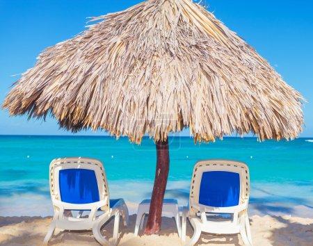 Sillas de playa y sombrilla de paja en la playa