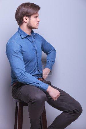Foto de Vista lateral de un joven hombre de la moda sentado en una silla y mirando hacia otro lado en el estudio - Imagen libre de derechos