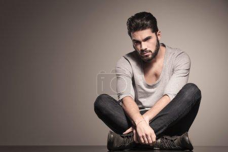 Photo pour Sérieux homme de mode barbu est assis en position de yoga sur le sol - image libre de droit