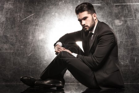 Photo for Serious young elegant man sitting and looking at the camera - Royalty Free Image